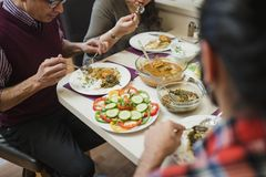 Family Eating Indian food Together. Close up shot of homemade indian food on a family dining table. They are eating curry with salad stock images