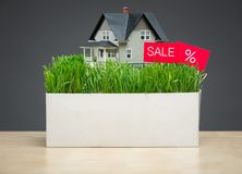 Close up shot of house model with grass and sale tablet Royalty Free Stock Photo