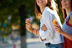 Close up shot of ice cream cones in hand of a woman standing with her friend. Two young women outdoors eating icecream Stock Image