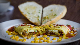 Close up shot of an Italian omelette with corn, garlic bread and more. Blurry background Royalty Free Stock Photos