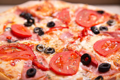 Close-up shot of Italian pizza with ham, tomatoes and olives Royalty Free Stock Images