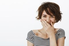 Close-up shot of joyful good-looking optimistic woman with short stylish haircut, laughing out loud or chuckling royalty free stock images