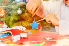 Kid`s hands with Christmas ornament and paintbrush stock photos