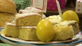 Close up shot of a lemon sponge cake with icing. Close up shot of a lemon sponge cake, with icing, on display, including real lemons for aesthetics stock video footage