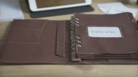 Close up shot of light brown leather note pad daily planner habit tracker bullet journal cell phone on wooden work table. Close up shot of light brown leather stock footage