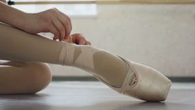 Close-up shot of little girl`s foot in pointe shoe and hands putting on professional footwear and tying ribbon around. Leg. Ballet-shoes, classical dancing and stock video