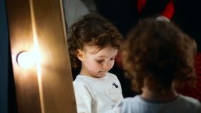 Close-up shot. Little girl stands at the mirror and looks a bit shy