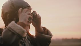 Close-up shot of little happy boy in old pilot costume wearing vintage aviation glasses in sunset field slow motion. Cheerful smiling excited male child stock video