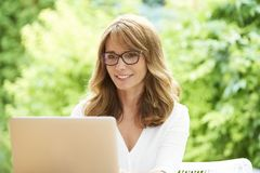 Happy mature woman with laptop. Close-up shot of a lovely attractive middle aged woman using laptop while sitting at home in the garden and relaxing Royalty Free Stock Image