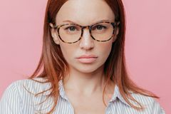Close up shot of lovely female model wears big optical glasses, has brown hair, looks seriously with confident expression, royalty free stock photography
