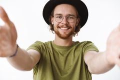 Close-up shot of lovely and happy young good-looking bearded pierced guy in glasses and hat pulling hands towards camera royalty free stock image