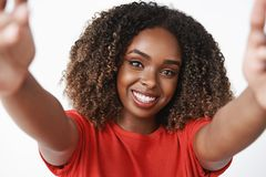Close-up shot of lovely tender and feminine african-american woman with curly hair in red t-shirt pulling hands and royalty free stock image