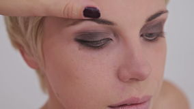 Close up shot. Make-up artist applying eyeliner around the entire eye of model stock video footage