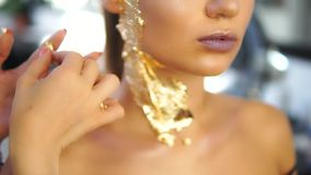 Close up shot of a makeup artist applying golden shiny pieces of metallic paper on a model`s face. Preparing for the. Fashion show. Dressing room for models stock footage