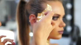 Close up shot of a makeup artist`s hands applying golden shiny pieces of metallic paper on a model`s face. Preparing for. The fashion show. Dressing room for stock video