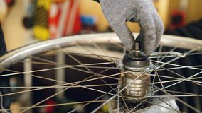 Close-up shot of male hand in protective glove assembling mechanism of bicycle wheel tightening up metal screw. Work. Close-up shot of male hand in greasy stock footage