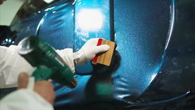 Close up shot of man applying vinyl film while tuning car. Close up shot of man applying vinyl film while tuning expensive blue car stock video footage