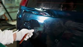 Close up shot of man applying vinyl film while tuning car. Close up shot of man applying vinyl film and heating it with a construction hair dryer while tuning stock video