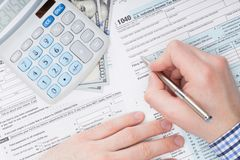 Close up shot of a male filling out US 1040 Tax Form next to calculator and 100 dollars banknote under it Stock Photos