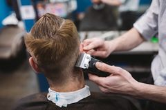 Close up shot of man getting trendy haircut at barber shop. Male hairstylist serving client, making haircut using machine and comb royalty free stock images