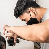 Close up shot of man getting trendy haircut. Male hairstylist serving client, making haircut using machine and comb. the concept. Of fashion and beauty royalty free stock photography