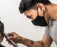 Close up shot of man getting trendy haircut. Male hairstylist serving client, making haircut using machine and comb. the concept. Of fashion and beauty stock images