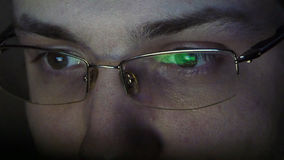 Close up shot of man in glasses surfing internet at night Stock Photography