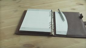 Close up shot of man hand putting silver ball pen into pen holder on light brown leather note pad planner bullet journal. Close up shot of man hand putting stock footage