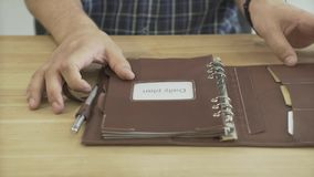 Close up shot of man hands opening elegant light brown leather daily planner journal note book pad on wooden table. Close up shot of elegant light brown leather stock video footage