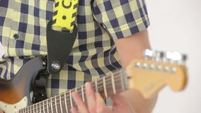 Guitar musician pluck the strings on electric guitar musical instrument. Close up shot of man hands playing on musical instrument isolated on white stock footage