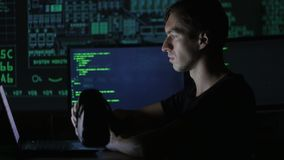 Male hacker programmer uses a virtual reality helmet for programming. IT Technologies of the Future. Close-up shot of a man in headphones getting experience in stock footage