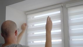 Close up shot of a man installing new blinds on his window in apartment. Checking the work. Striped blinds on the window stock video footage