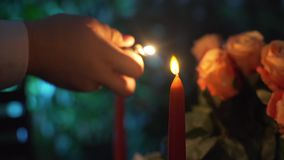 Close up shot of a man that lights candles. Valentines day. making a marriage proposal. Two candles and bouquet of roses on a table stock video