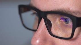 Close up shot of a man`s eyes with eyeglasses looking at a monitor