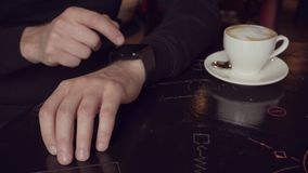 Close up shot of man`s hand with smart watch near the cup of coffe in small cafe stock video