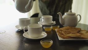 Close up shot of a man`s hands, he is having breakfast at the table, pouring tea. Close up shot of the man`s hands, a man has breakfast in the hotel room, he stock footage