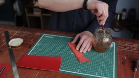 Leathersmith is applying glue on a leather parts of the zipper with a special brush. He works at the table in the. Close up shot of the man`s hands, who cuts off stock video