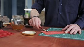Leathersmith is applying glue on a leather parts of the zipper with a special brush. He works at the table in the. Close up shot of the man`s hands, who cuts off stock video footage