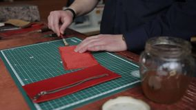 Leathersmith is applying glue on a leather parts of the zipper with a special brush. He works at the table in the. Close up shot of the man`s hands, who cuts off stock footage