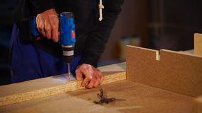 Close up shot of male hands, carpenter uses electric drill in workshop. Close up shot of the man`s hands, who works with the chipboard to then screw in the panel stock footage