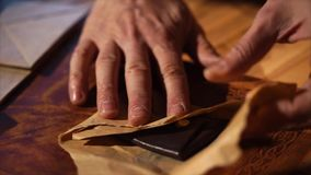 Close up shot of a man`s hands, who wraps in a craft paper handmade purse. Close up shot of the leather case of the master of the hand, who wraps in the craft stock video footage