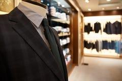 Close up shot of man suit jacket on hanger. Close up shot of blue man jacket and grey shirt with tie on hanger in wardrobe Stock Photos