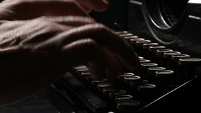 Close up shot of man typing on old vintage retro typewriter; news, media or communication concept