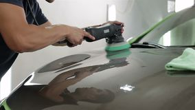 Close up shot of a man waxing hood of the car with special tool. stock video footage