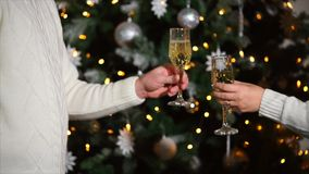 Close up shot of the man and woman hands, who clink glasses of champagne near the New Year tree. Close up shot of women and men hands who holds glasses with stock video