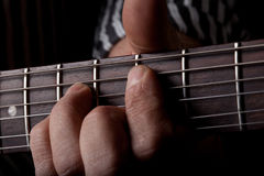 Close up shot of a mans left hand playing guitar Royalty Free Stock Photos