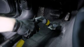 Close up shot of a master in gloves using washing vacuum cleaner for car`s headliner. Washing pedals. Dry-cleaning service stock video footage