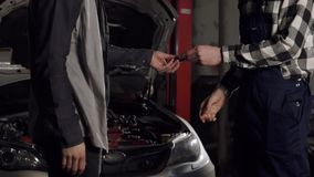 Close Up shot of mechanic and customer shaking hands in an auto repair shop. stock video