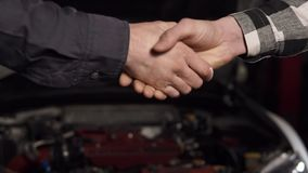 Close up shot of mechanic and customer shaking hands in an auto repair shop. stock video footage