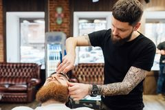 Man getting trendy haircut at barber shop. Close up shot of men getting trendy haircut with a dangerous razor at barber shop. The male hairstylist in tattoos Royalty Free Stock Photos
